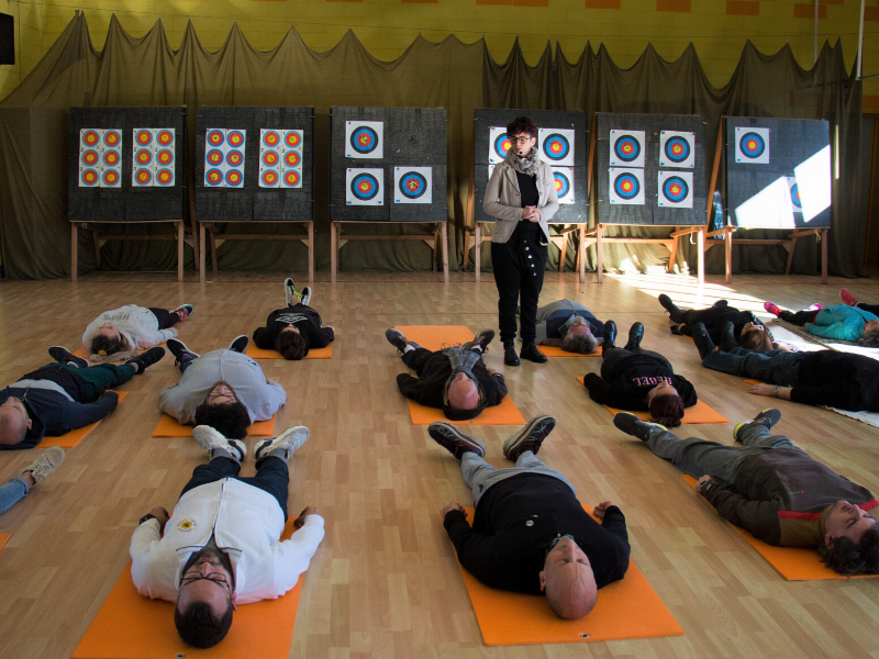 Silvia Rizzi e gli atleti della Compagnia Arcieri Padovani che eseguono distesi sui materassini le tecniche di allenamento mentale